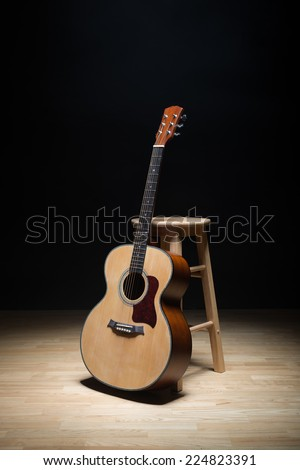 Acoustic guitar on the floor. - stock photo