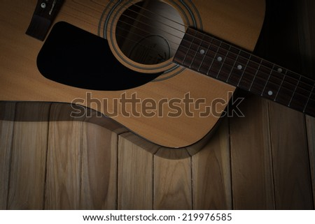 acoustic guitar on wooden background in lowkey light effect and vignett style