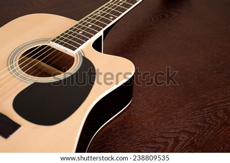 Acoustic guitar on wooden table close up - stock photo