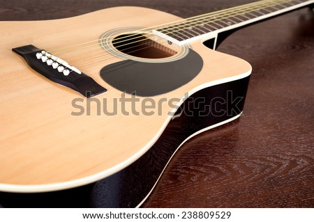 Acoustic guitar on wooden table close up. selective focus - stock photo