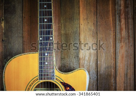 Acoustic guitar on wooden wall background with copy space