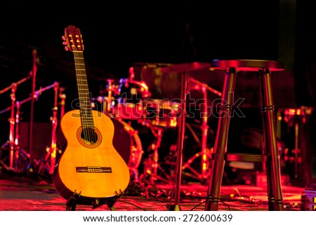 Acoustic guitar over blurry music stage background - stock photo