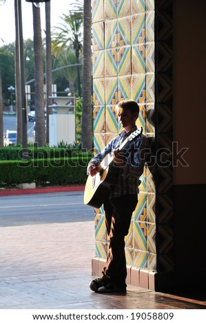 Acoustic guitar player leans against a bright tile doorway