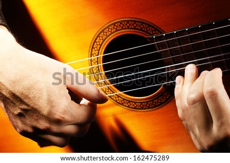Acoustic guitar playing details with classical guitarist hands close up - stock photo