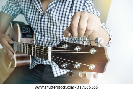 Acoustic Guitar Playing. Men tune Acoustic Guitar, Closeup with hand - stock photo