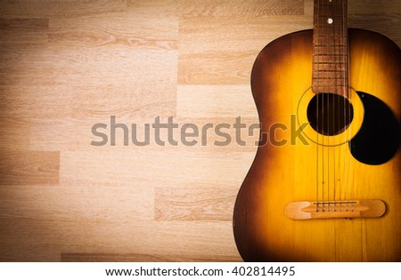 Acoustic guitar resting against a blank grunge background with copy space