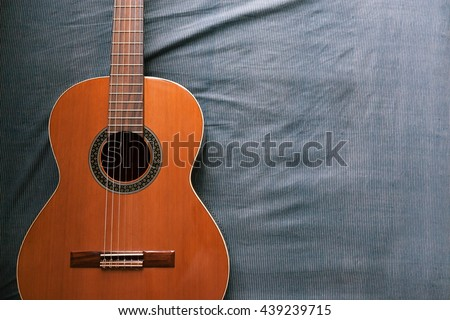 Acoustic guitar resting against a fabric background with copy space - stock photo
