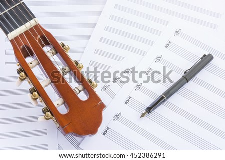 Acoustic guitar, sheet music and fountain pen on wooden table, flat lay