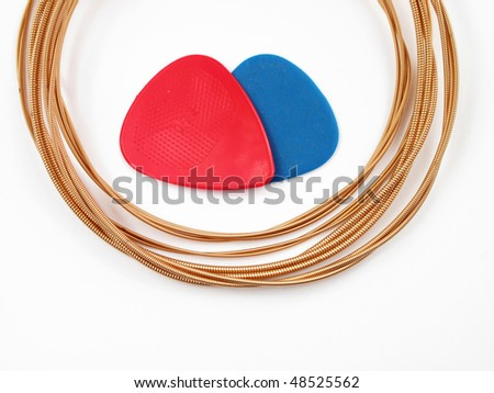 Acoustic guitar strings and plectrums on white background - stock photo