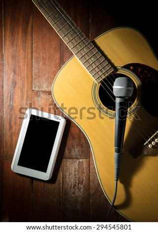 Acoustic guitar with microphone and computer tablet. - stock photo