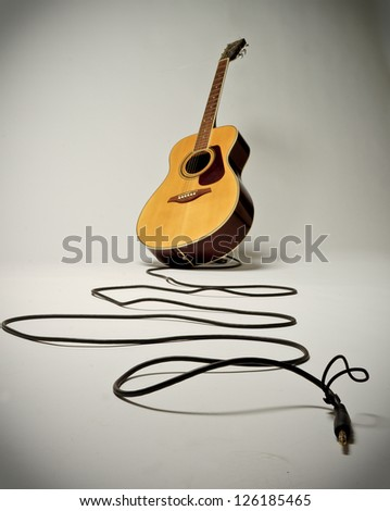 Acoustic guitar with trailing lead on white backdrop - stock photo
