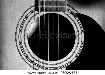 Acoustic Guitar with very shallow depth of field, focus on strings. Black & White - stock photo