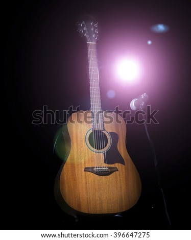 Acoustic wooden a guitar over black background.