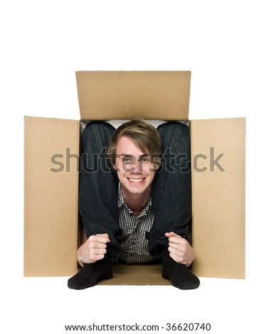 Acrobat inside of a cardboard box. - stock photo