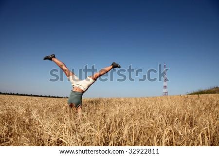 acrobatic girl at field near radio antenna - stock photo