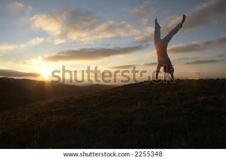 Acrobatic girl on grassland of sunrise - stock photo