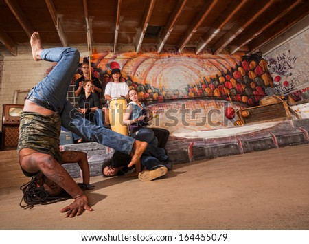 Acrobatic group of capoeira performers in building - stock photo