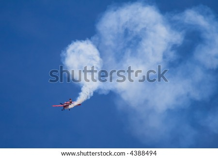 Acrobatic plane doing loops with lots of smoke behind it