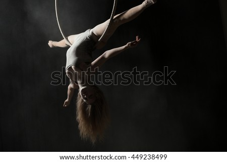 Acrobatic woman doing gymnastic cross twine on aerial hoop - stock photo