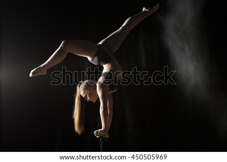 Acrobatic woman handstand on equilibr stand - stock photo