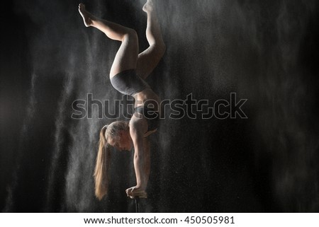 Acrobatic woman handstand on equilibr while sprinkled flour - stock photo