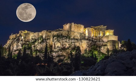 Acropolis in the moonlight. Night. The full moon and the light of lanterns light up the Acropolis. The trees in the background and lighting. In the foreground is the ancient stones in the moonlight. - stock photo