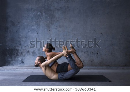 Acroyoga practice, man and woman practice bow pose on a urban background - stock photo