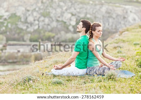 Acroyoga. Woman and man doing yoga on mountain - stock photo