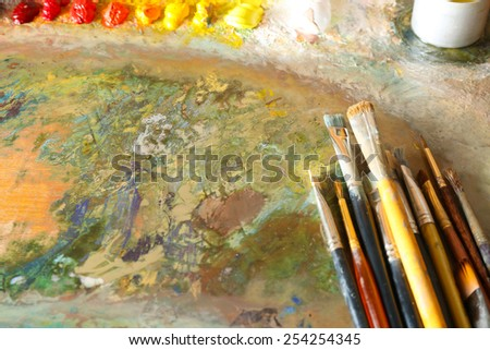 Acrylic paint with brushes on wooden palette - stock photo