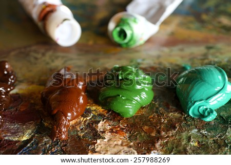 Acrylic paint with paint tubes on wooden palette - stock photo