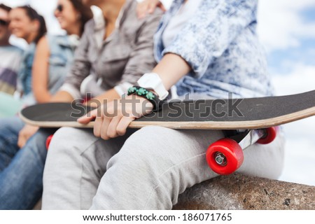 acticity and summer holiday concept - close up of female hand holding skateboard - stock photo