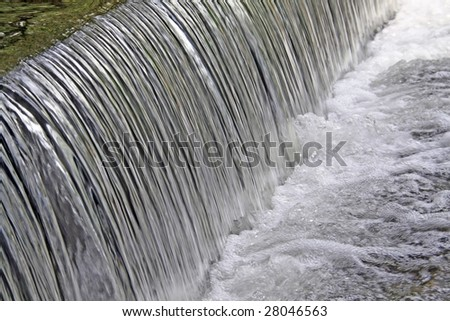 Action (frozen) shot of a small waterfall in a nature reserve - stock photo