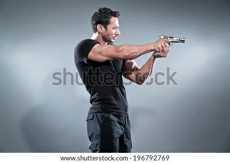 Action hero muscled man shooting with gun. Wearing black t-shirt and pants. Studio shot against grey. - stock photo