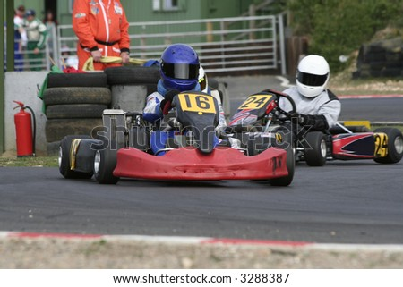 Action in a bend at a go kart race with marshall in background - stock photo
