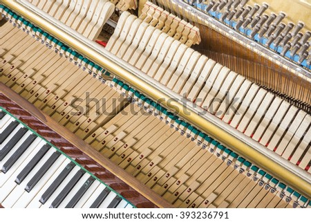 Action mechanics close up inside of an upright piano. Pattern of keys, shanks, hammers and strings. - stock photo