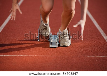 Action packed image of a female athlete leaving the starting blocks for a sprint run on a track - stock photo