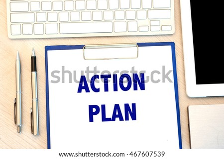 action plan written on board with keyboard, tablet and pen on wooden table background
