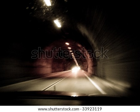 Action point of view shot of interior of tunnel with lights extending into the horizon - stock photo