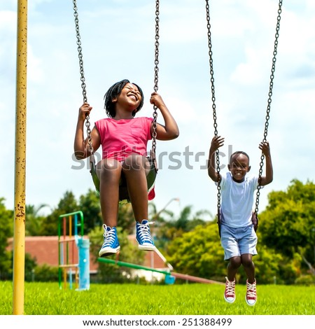 Action portrait of African kids having fun swinging in park.Out of focus houses in background. - stock photo