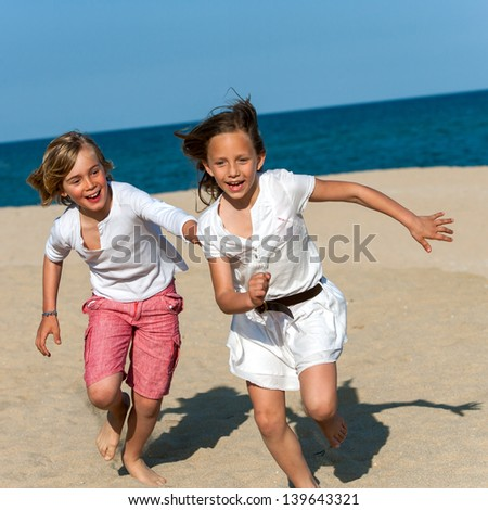 Action portrait of boy and girl having fun on beach chasing. - stock photo