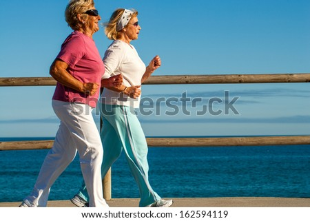 Action portrait of elderly women jogging together outdoors.