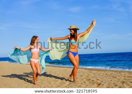 Action portrait of Joyful young girls running with color foulard's. Young mother with daughter on holiday at beach. - stock photo