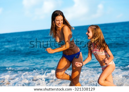 Action portrait of two Young girls having great time on beach. Girls running and splashing water. - stock photo