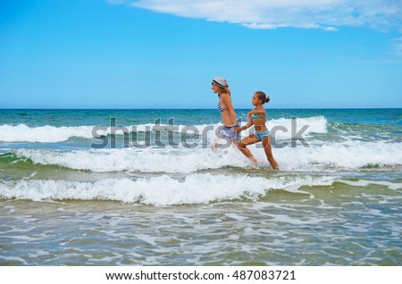 Action portrait of two Young girls having great time on beach. Girls running and splashing water.  Concept of friendly family.