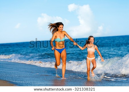 Action portrait of two young happy women running and splashing water  along beach. - stock photo