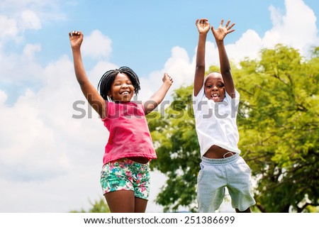 Action portrait of young African boy and girl jumping in park. - stock photo