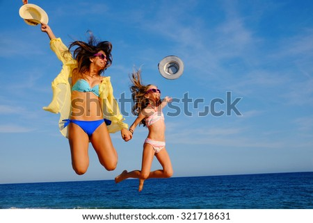 Action portrait of young mother with daughter  jumping together on beach. Laughing girls in swimwear throwing hats in air.
