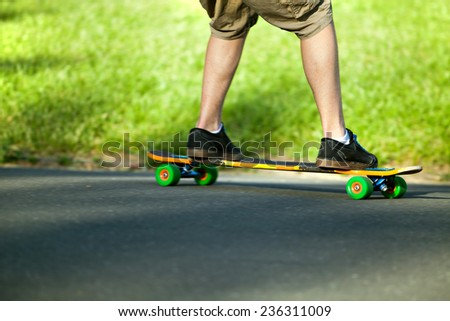 Action shot of a longboarder skating on a suburban road. Shallow depth of field.  - stock photo