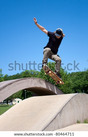Action shot of a skateboarder performing a jump at a skate park. - stock photo
