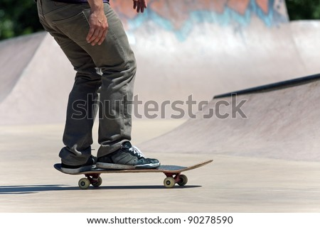 Action shot of a skateboarder skating at the skate park with concrete ramps.